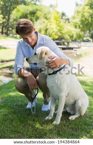 Handsome man with his labrador in the park on a sunny day - stock photo