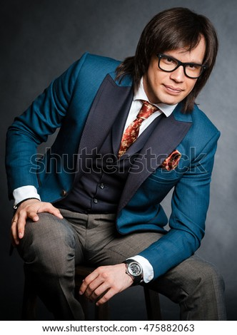 handsome man with long hair brunette and brown eyes in black rim eyeglasses blue suit and red tie sitting and looking forward with hand on his leg at black background