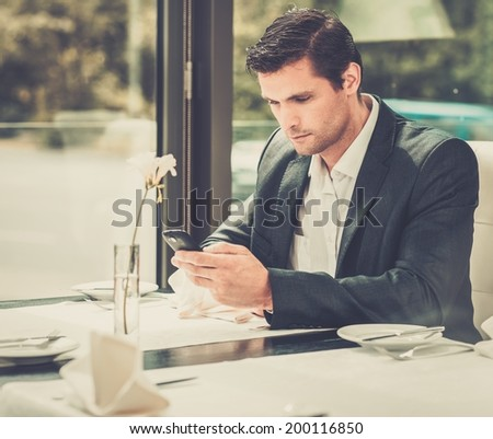 Handsome man with mobile phone in restaurant