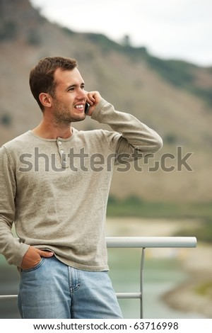 Handsome man with mobile phone outdoors - stock photo