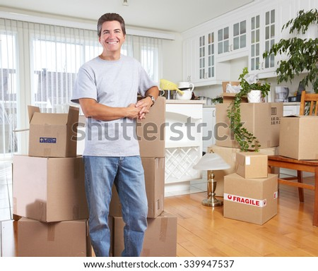 Handsome Man with moving boxes in new modern apartment.