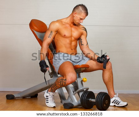 Handsome man with muscles lift a dumbbell on a seat trainer - stock photo