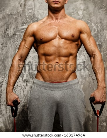 Handsome man with muscular body doing fitness exercise  - stock photo