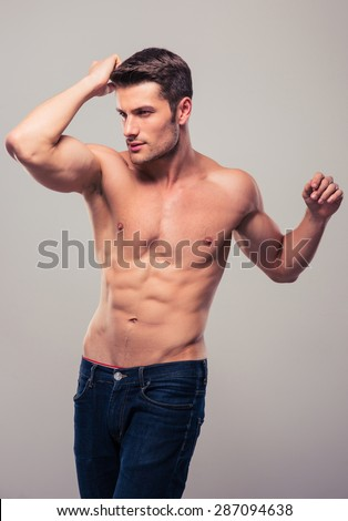 Handsome man with muscular body posing over gray background - stock photo