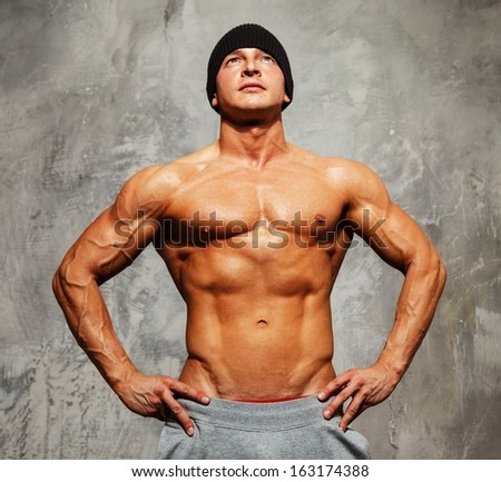 Handsome man with muscular torso in beanie hat posing  - stock photo