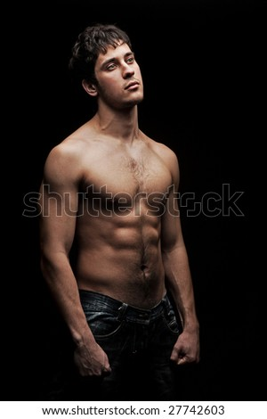 handsome man with naked torso against black background - stock photo