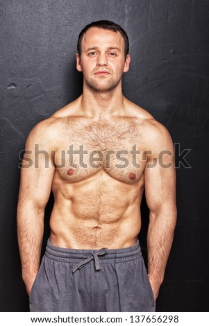 Handsome man with naked torso posing in studio - stock photo