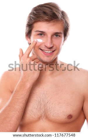 Handsome man with naked torso smiling and applies cream on his face - stock photo