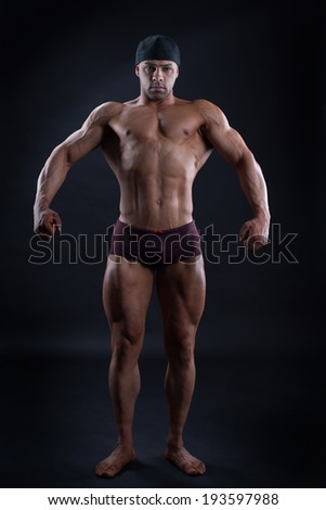 Handsome man with perfect powerful body demonstrates his strong muscles