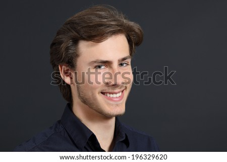 Handsome man with perfect white smile on dark gray background - stock photo