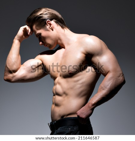 Handsome man with sexy muscular beautiful body posing at studio.
