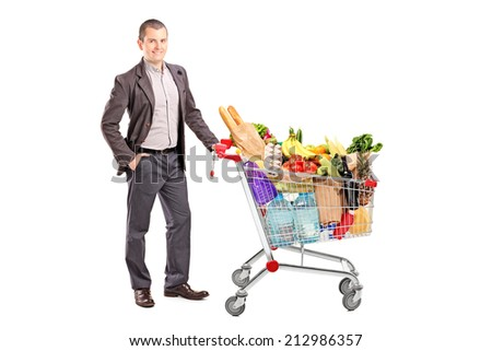 Handsome man with shopping cart full of groceries isolated on white background