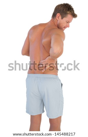 Handsome man with shorts suffering from back pain on white background