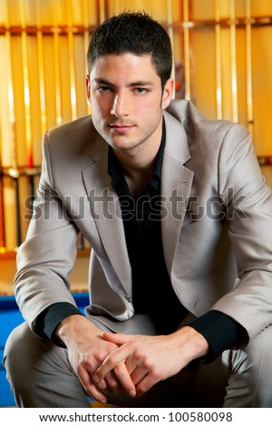 handsome man with suit sitting posing in billiard pool in club - stock photo