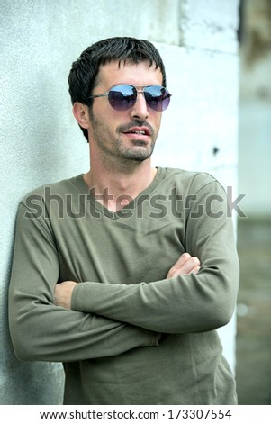 Handsome man with sunglasses posing on white wall - stock photo