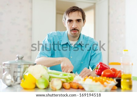 handsome  man with vegetables in domestic kitchen at home  - stock photo
