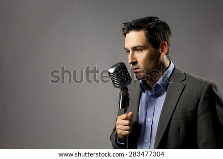 handsome man with vintage microphone in gray suit on gray background - stock photo