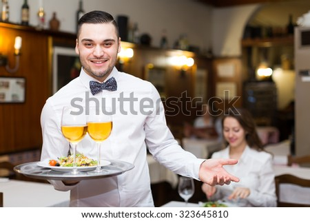Handsome man working as a waiter in a restaurant. He wearing white shirt with a bowtie and holding a tray in his hand - stock photo