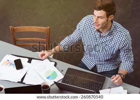 Handsome man working at a table in the office with his laptop computer and analytical business graphs, high angle view - stock photo
