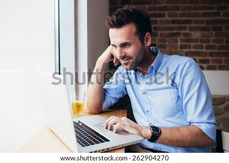 Handsome man working on laptop at office - stock photo