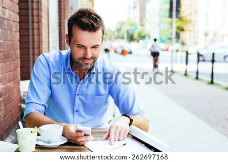 Handsome man working with smartphone and documents at outdoor cafe - stock photo