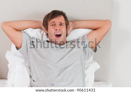Handsome man yawning in his bedroom - stock photo
