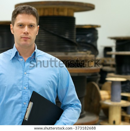 Handsome manager at electrical wire and cable factory. - stock photo