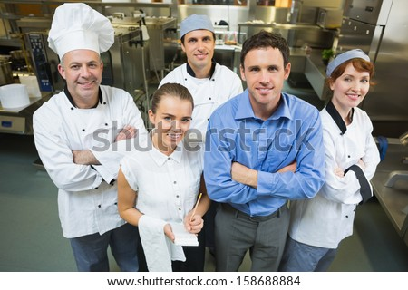 Handsome manager posing with some chefs and waitress in a kitchen - stock photo