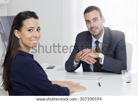 Handsome  manager sitting at a desk opposite young businesswoman and they are  looking at camera. - stock photo