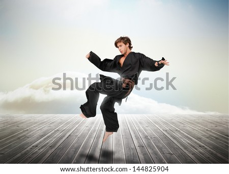 Handsome martial arts fighter over wooden boards leading out to the horizon - stock photo