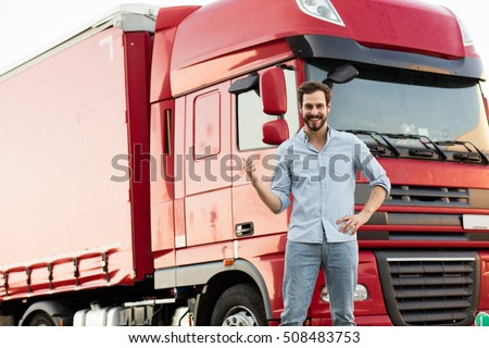handsome masculine truck driver standing outside with his vehicle behind with pointing his car