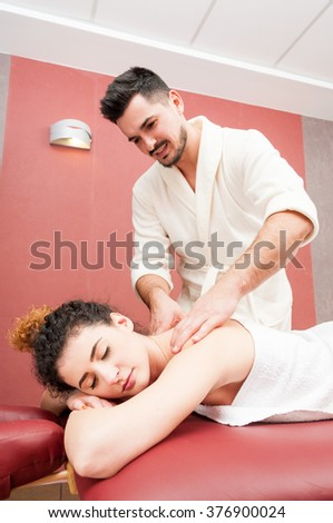 Handsome masseur getting a back massage to his girlfriend in the spa resort