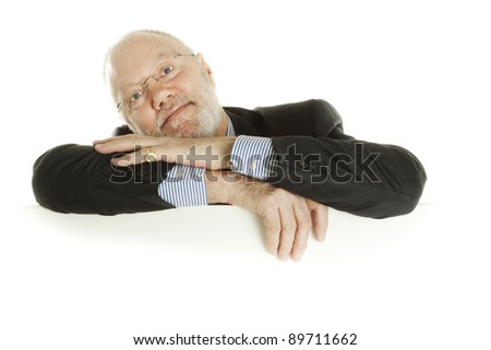 Handsome mature business man posing behind blank banner on white background - stock photo