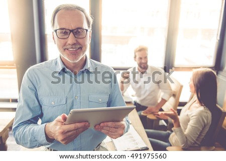 Handsome mature businessman in eyeglasses is using a digital tablet, looking at camera and smiling, his colleagues are working in the background