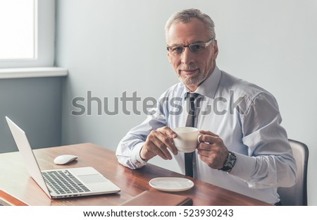 Handsome mature businessman in formal suit and glasses is holding a cup, looking at camera and smiling while working with a laptop in office