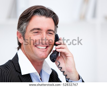 Handsome mature businessman talking on phone sitting at his desk