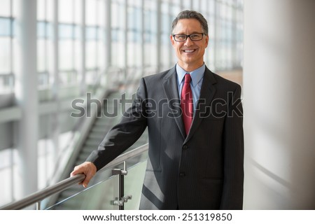 Handsome mature businessman with glasses smiling  - stock photo