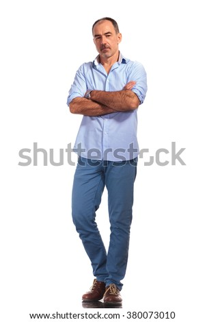 handsome mature casual man posing with hands crossed while looking at the camera in white isolated studio background - stock photo