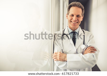 Handsome mature doctor in white coat is looking at camera and smiling while standing with crossed arms in hospital corridor
