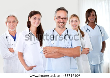 Handsome mature doctor smiling at the camera with folded hands and colleagues in background