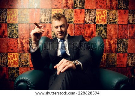Handsome mature man in elegant suit smoking a cigar. He is sitting on a leather chair in a luxurious interior.  - stock photo