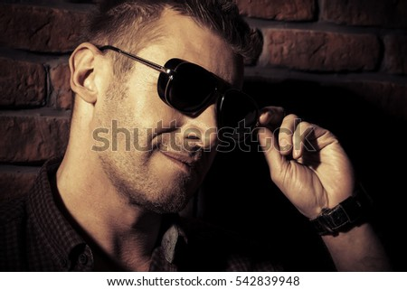 Handsome mature man in sunglasses standing by the brick wall. Men's beauty, fashion.