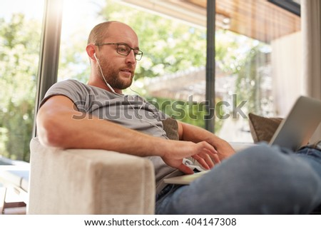 Handsome mature man using his laptop while relaxing at home, he is with earphones sitting on sofa at home. - stock photo