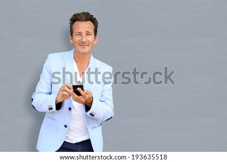 Handsome mature man using smartphone, isolated - stock photo