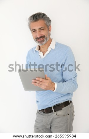 Handsome mature man websurfing with tablet, isolated - stock photo
