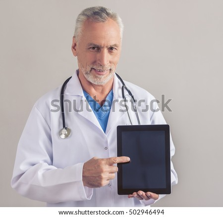 Handsome mature medical doctor in white medical coat is holding a digital tablet, looking at camera and smiling, on gray background