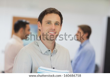 Handsome mature student posing in classroom smiling at camera - stock photo