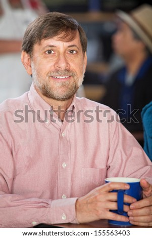 Handsome mature white male holding coffee mug