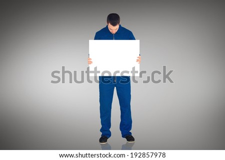 Handsome mechanic showing card against grey vignette - stock photo