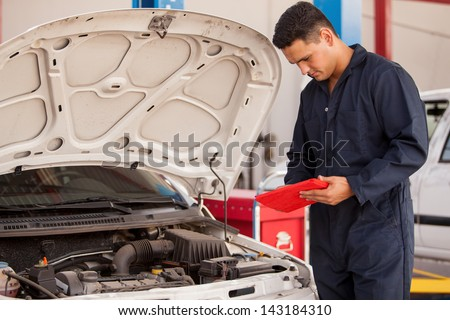 Handsome mechanic using a tablet computer for work in an auto shop - stock photo
